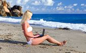 Sexy Beautiful Woman In Bikini Using Laptop At The Beach