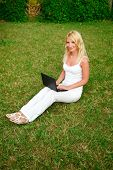 Young Beautiful Woman Working With Laptop In The Green Grass