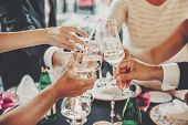 Hands Toasting With Champagne Glasses At Wedding Reception Outdoors In The Evening. Family And Frien poster