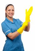 Smiling cleaning lady putting on the rubber gloves isolated on white