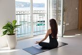 Young Woman Is Practicing Yoga In Front Of Big Opened Window With View Of Sea Beach, Mountains. Girl poster