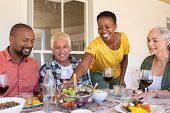 Cheerful black woman serving bowl of fresh salad to guests during lunch. Mature woman serving food w poster