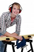 Female carpenter wearing protective muffs