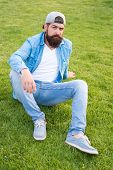 Stylish And Comfortable To Wear. Stylish Hipster In Baseball Cap Sitting On Green Grass Outdoor. Bea poster