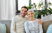 family, generation and people concept - happy smiling senior mother with adult son hugging at home poster