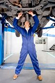foto of chassis  - Mechanic working on a cars chassis at the garage - JPG