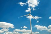 Electricity wind generator on bright cloudy sky background - wind energy and technology concept poster
