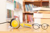 Glasses And Headphones As Audio Books Concept On  High School Or University Library Background poster