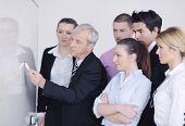 Homem de negócios sênior masculino, dando uma apresentação em uma reunião no escritório de luz moderna em uma placa de mesa