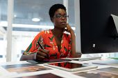 Front view of young African american female graphic designer working on graphic tablet at desk in of poster