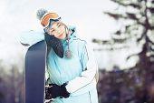 Junge Frau mit Snowboard im Sonnenlicht
