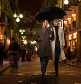 stock photo of overcoats  - Elegant couple with umbrella outdoors on rainy evening - JPG