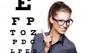 woman with blue trendy glasses on the background of eye test chart