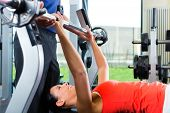 Woman with her personal fitness trainer in the gym exercising with dumbbells, she is using barbell o