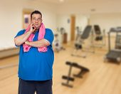 stock photo of morbid  - Pensive fat man playing sport in the gym - JPG