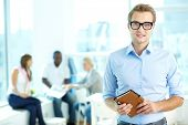 Portrait of handsome man in eyeglasses holding notepad and looking at camera in working environment