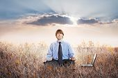 image of enlightenment  - Businessman meditating in lotus pose - JPG
