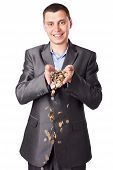 Young Smiling Businessman With Heap Of Coins Isolated On White Background