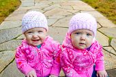 stock photo of beanie hat  - Two twin baby girls sit on a stone walkway wearing pink sweatshirts and beanies - JPG