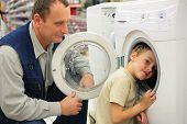 Man Looks At Washing Machine In Store Boy Glances Inward It