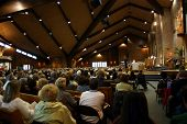 image of pews  - a full house of people attend a church mission and listen intently to priest - JPG