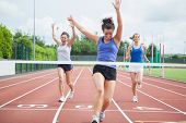 stock photo of track field  - Female athlete celebrates win at finish line at track field - JPG