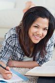 Frau lächelnd als She legt auf den Boden und Schreibvorgänge auf einem Notebook in einem Wohnzimmer