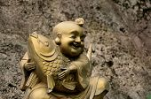 Golden laughing Buddhist monk with fish symbolizing good fortune