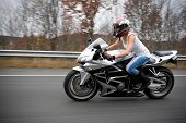 pic of crotch-rocket  - A pretty blonde girl in action driving a motorcycle at highway speeds - JPG