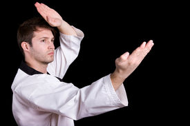 picture of shotokan  - Young man practicing martial arts over black background - JPG