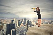 stock photo of spyglass  - career woman looking with binoculars over the city - JPG