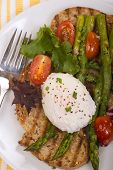 Poached egg on toasted bread with asparagus, tomatoes, greens