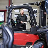 An experienced and reliable mechanic, with a clipboard and pen in his hand, working on a forklift at