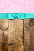 Colorful fabric with color ribbon and bow on wooden background