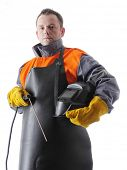 Portrait of welder wearing protective welding black leather apron, welding hood and welding electrod