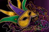 picture of mardi gras mask  - glittery gold green and purple mardi gras mask with beads on a purple background - JPG
