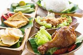 Famous traditional Indonesian food. Delicious nasi ayam penyet with sambal belacan. Fresh hot with s