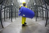 technician protective overalls,mask,gloves and boots lifting barrel of chemicals in empty storehouse