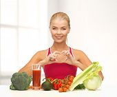 fitness, diet and food concept - smiling woman with organic food showing heart shape with hands
