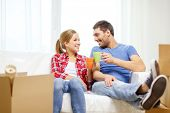 moving, home and couple concept - smiling couple with coffee or tea cups relaxing on sofa in new hom