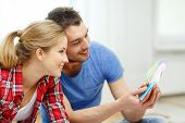 repair, interior design, building, renovation and home concept - smiling couple looking at color sam
