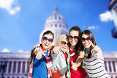 summer, holidays, vacation, happy people concept - beautiful teenage girls or young women showing th