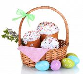 Beautiful Easter cakes in basket, colorful eggs and pussy-willow twigs isolated on white