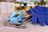 Construction stapler and gloves on fabric on bright background