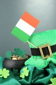 Saint Patrick day hat, pot of gold coins and Irish flag on grey background