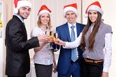Successful young businesspeople at Santa hat at office