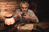 picture of tobacco-pipe  - Senior man with smoking pipe in homely wooden interior - JPG
