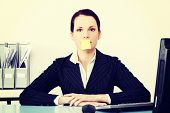 Pretty caucasian businesswoman sitting in the office with post it note on her mouth.