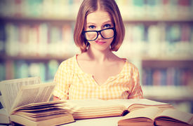 stock photo of schoolgirl  - funny crazy girl student with glasses reading books in the library - JPG