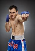 stock photo of muay thai  - Caucasian kickboxer or muay thai fighter executing a punch on gray background - JPG